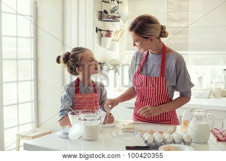 Mom with her 9 years old daughter are cooking in the kitchen to Mothers day, lifestyle photo series