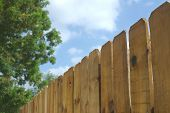 stock photo of wooden fence  - a wooden fence with a green tree and a cloudy sky - JPG
