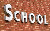 stock photo of school building  - white school sign on a brick wall - JPG