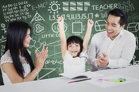 stock photo of applause  - Photo of two proud and happy parents giving applause on their daughter after finishing schoolwork - JPG