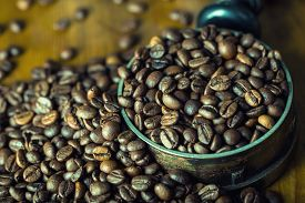 picture of coffee grounds  - Coffee. Coffee beans. Roasted coffee beans spilled freely on a wooden table. Coffee beans in a dish for ground coffee.