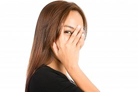 picture of shy woman  - Closeup portrait of playful Asian woman looking at camera peeking out through split fingers hand covering face showing fear interest shy curiosity playing peekabo - JPG