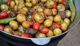 stock photo of cauldron  - Big cauldron with roasted potato, meat and tomato ** Note: Shallow depth of field - JPG