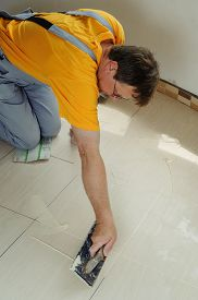 picture of grout  - The worker holding a rubber float and filling joints with grout - JPG