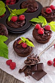 stock photo of chocolate muffin  - Chocolate raspberry yogurt muffins with pieces of chocolate and muffin tin - JPG