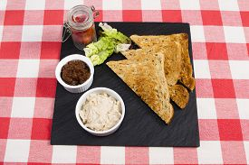 picture of canard  - a pot of creamy salmon pate on a slate plate with pickle and triangles of toast - JPG