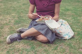 stock photo of eat grass  - A young woman is sitting on the grass in a park and is eating falafel - JPG