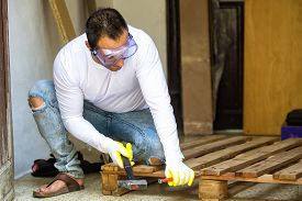 stock photo of chisel  - Man dismantled a pallet with hammer and chisel - JPG