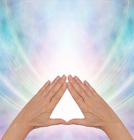 picture of triangular pyramids  - Female hands making a triangle shape on a misty blue flowing triangular shaped energy field with plenty of copy space above - JPG