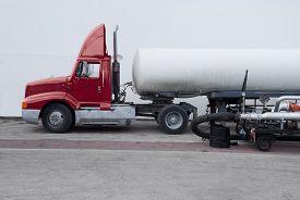 image of fuel tanker  - Fuel truck tanker refueling large cruise ship - JPG
