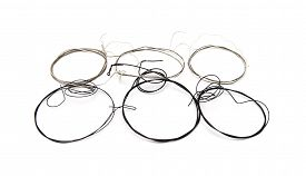 stock photo of nylons  - Old nylon classical guitar strings isolated on white - JPG