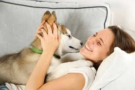 picture of laika  - Woman lying with her malamute dog on sofa in room - JPG
