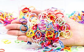 picture of rubber band  - hands and pile of small round colorful rubber bands rainbow color for making rainbow loom bracelets on the table - JPG