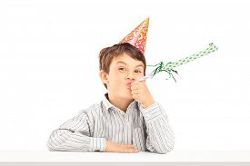 picture of spoiled brat  - Little kid with party hat sitting at a table and blowing a favor horn isolated on white background - JPG