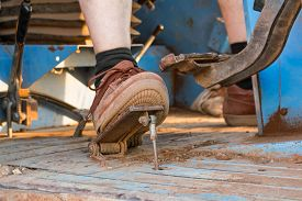 stock photo of pedal  - Human foot on the pedal of a tractor - JPG