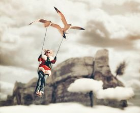 foto of surrealism  - a pretty girl being carried on a swing by two seagulls in a surreal digital manipulation with a cliff and clouds in the background  - JPG