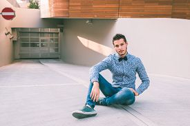 stock photo of bow tie hair  - Young handsome man with short hair wearing a bow tie and posing in the city streets - JPG