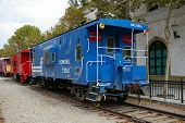 image of caboose  - Picture of an old blue caboose parked at a train station.