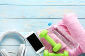 Green Dumbbells With Towel, Bottle And Smartphone With Headphones On Wooden Table poster