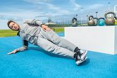 Planking fitness man doing side plank exercises at outdoor gym training obliques muscles on floor. B poster