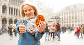 Young Beautiful Female Tourist Holds A Traditional Belgian Waffle With One Hand And Shows A Thumbs U poster