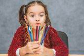 Close-up Concept Of Colored Pencils In The Hands Of The Girl That Holds Them On The Level Of The Fac poster