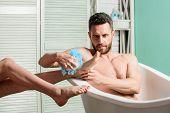 Guy Wash Female Legs With Foam Sponge. Macho Enjoying Bath. Sexy Man In Bathroom. Sex And Relaxation poster