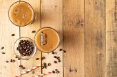 Flat Lay. Cold Coffee In Transparent Glasses With Ice And Straws, On A Wooden Background, Cooling Dr poster