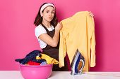 Busy Hard Working Black Haired Housewife Doing Ironing After Laundry, Holding Ironed Yellow Shirt, B poster