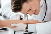 Cheerful Dermatologist Examining Hand Of Woman While Holding Dermatoscope poster