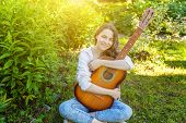 Young Hipster Woman Sitting In Grass And Playing Guitar On Park Or Garden Background. Teen Girl Lear poster