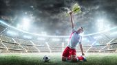 Soccer Player Celebrates Winning The Open Stadium. Soccer Player Holds A Trophy One Hand . Medal On  poster