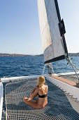 Beautiful Woman Relaxing On A Summer Sailing Cruise, Sitting And Sunbathing In Hammock Of Luxury Cat poster
