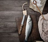 Fresh Whole Sea Bass Fish And Knife On Brown Cutting Board , Top View poster