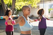 Group of curvy women in training session of aerobics using dumbbells at park. Bald woman doing exerc poster