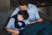Father With Little Son Sitting On The Sofa. Fathers Day. Happy Young Father Embracing Kid Sitting On poster