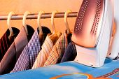 Colored Shirts On The Hanger, Electric Iron, Ironing Board In The Laundry Room. Ironing After Washin poster