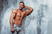 Portrait Of Strong Healthy Handsome Athletic Man. Fitness Model Posing And Smiling Near Gray Wall. F poster