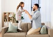 family, childhood and fatherhood concept - happy father and little daughter jumping on sofa and havi poster