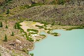 Lake Of Old Turquoise Color Near Stone Slope Of Mountain With Bog Terrain. Smooth Surface Of Water O poster