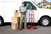 Smiling delivery courier standing near the white truck. Shipping service.