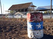 image of barrel racing  - An old painted barrel in a rural rodeo arena - JPG