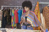 stock photo of palm-reading  - Attractive African American female fashion designer using cell phone - JPG