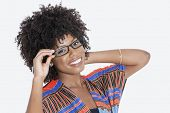 pic of traditional attire  - Portrait of young woman in African print attire wearing glasses over gray background - JPG