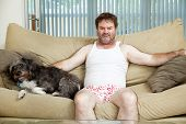 Discouraged unemployed man at home in his underwear, sitting on the couch with his dog.