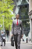 Happy African American businessman with bag walking on street
