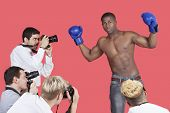 stock photo of partially nude  - Paparazzi taking photographs of male boxer over red background - JPG