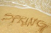 stock photo of spring break  - A warm tropical beach for spring break concept and spring written in the sand - JPG
