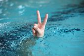 Body language.Hand with two fingers up in the  victory or peace symbol,above water surface