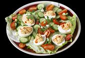 Closeup view of a salad of deviled eggs served with lettuce, miniature tomatoes, sliced cucumber and